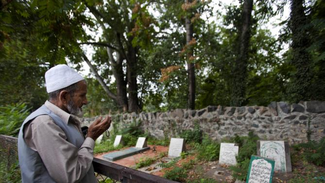 """A Kashmiri Muslim prays near an unmarked grave, right foreground, inside a martyrs graveyard in Srinagar, India, Wednesday, Sept. 5, 2012. The government of Kashmir has rejected wide-scale DNA testing of bodies in thousands of unmarked graves despite pleas by the families of those who disappeared during two decades of fighting in the restive region. The Tombstone reads, """"unidentified fifteen year old boy shot and killed by Border Security Force soldiers on 5th September 2003."""" (AP Photo/ Dar Yasin)"""